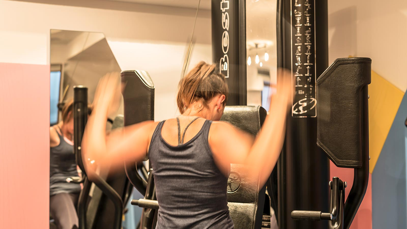 A girl is working out at the gym of Hotel Maibad in Vipiteno